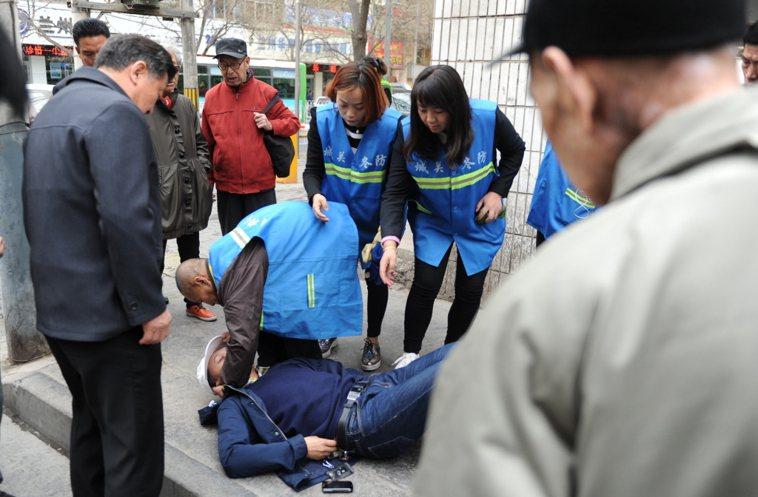 蘭州一男子昏倒,眾人通過掐人中等急救措施對其施救。中新社