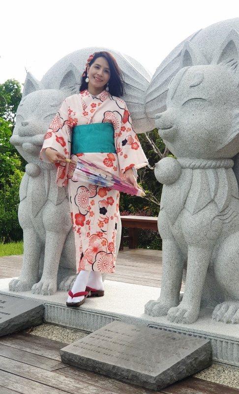 藍心瑩走進御守亭,身旁是綠舞吉祥物狛狐石雕。 徐谷楨/攝影