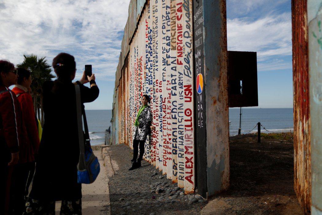 美墨邊界牆也成為大陸觀光客到此一遊的拍照景點。 (路透)