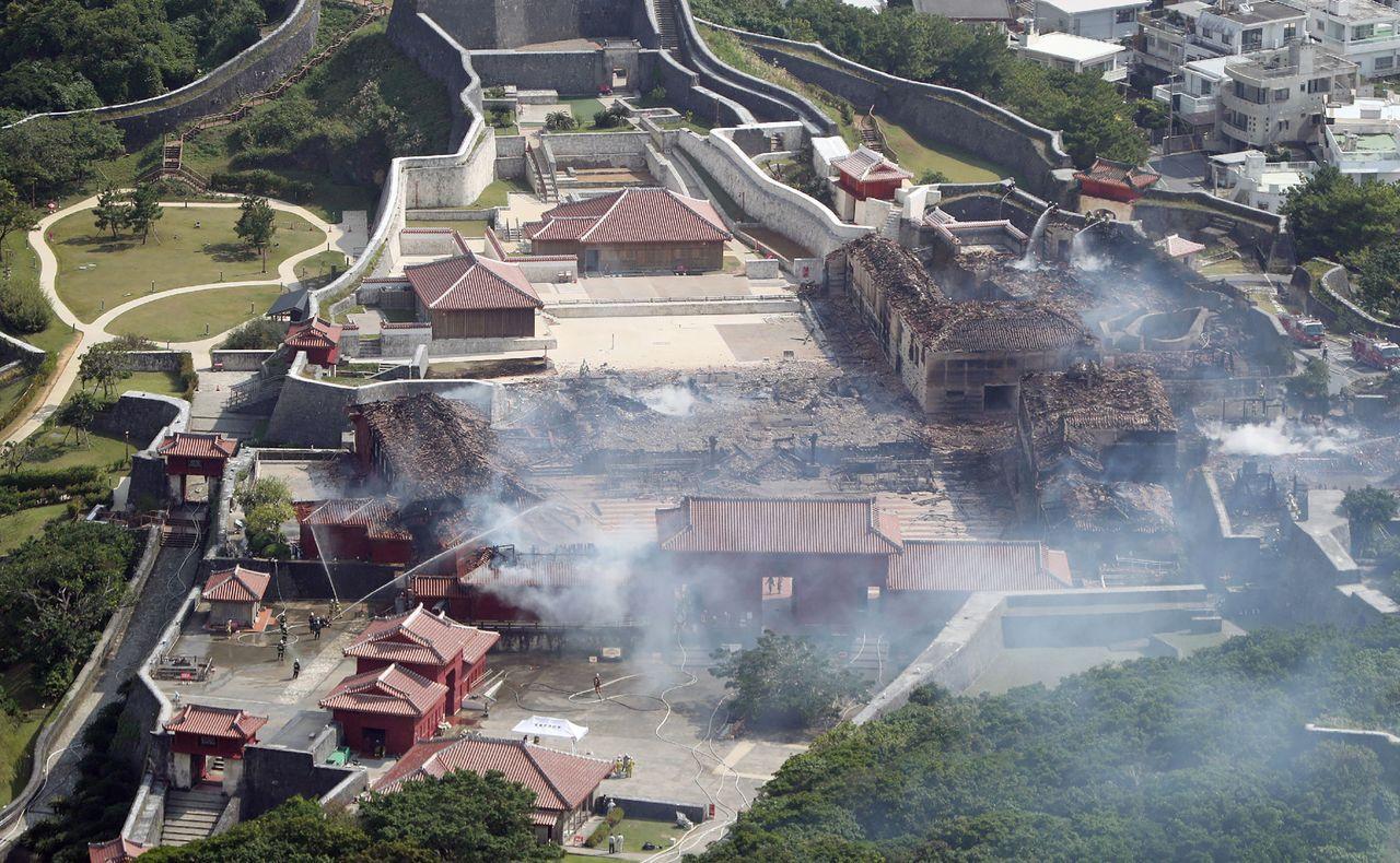 首里城慘遭祝融,消防隊控制火勢後,火場仍不斷冒出濃煙。法新社