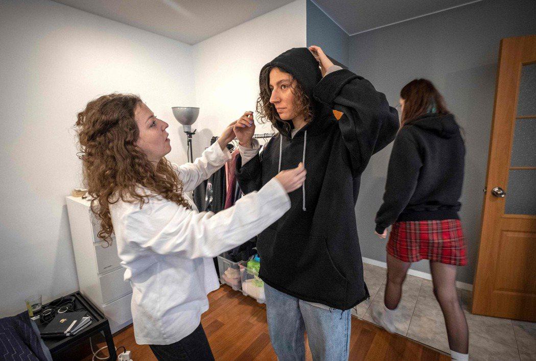 時尚設計師穆濟琴科(左)在莫斯科工作室為模特兒調整服裝。 (法新社)