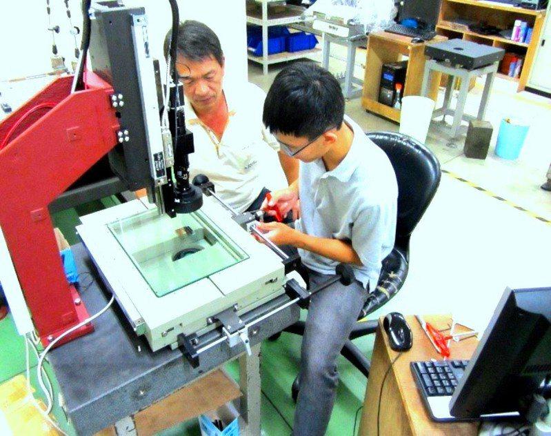 前年參加就業儲蓄方案的彰中畢業生陳俊廷(右),工作時由職場導師指導量測儀的機構調整。圖/陳俊廷提供