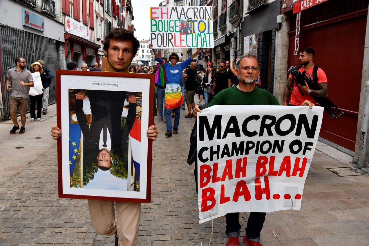 兩名抗議者分別拿著馬克宏玉照及寫有「馬克宏是廢話之王」海報。 (法新社)
