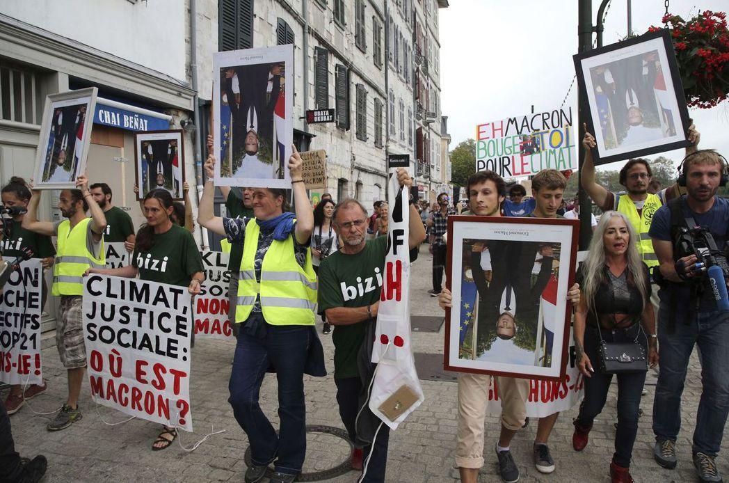 抗議氣候變遷的示威者故意將馬克宏玉照拿反,指其「表裡不一」的氣候政策。 (美聯社...