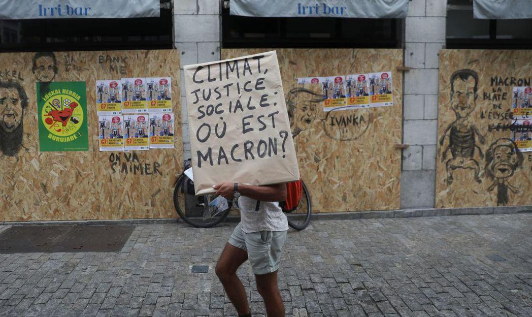 一位環保示威者拿著批評馬克宏的海報。 (路透)