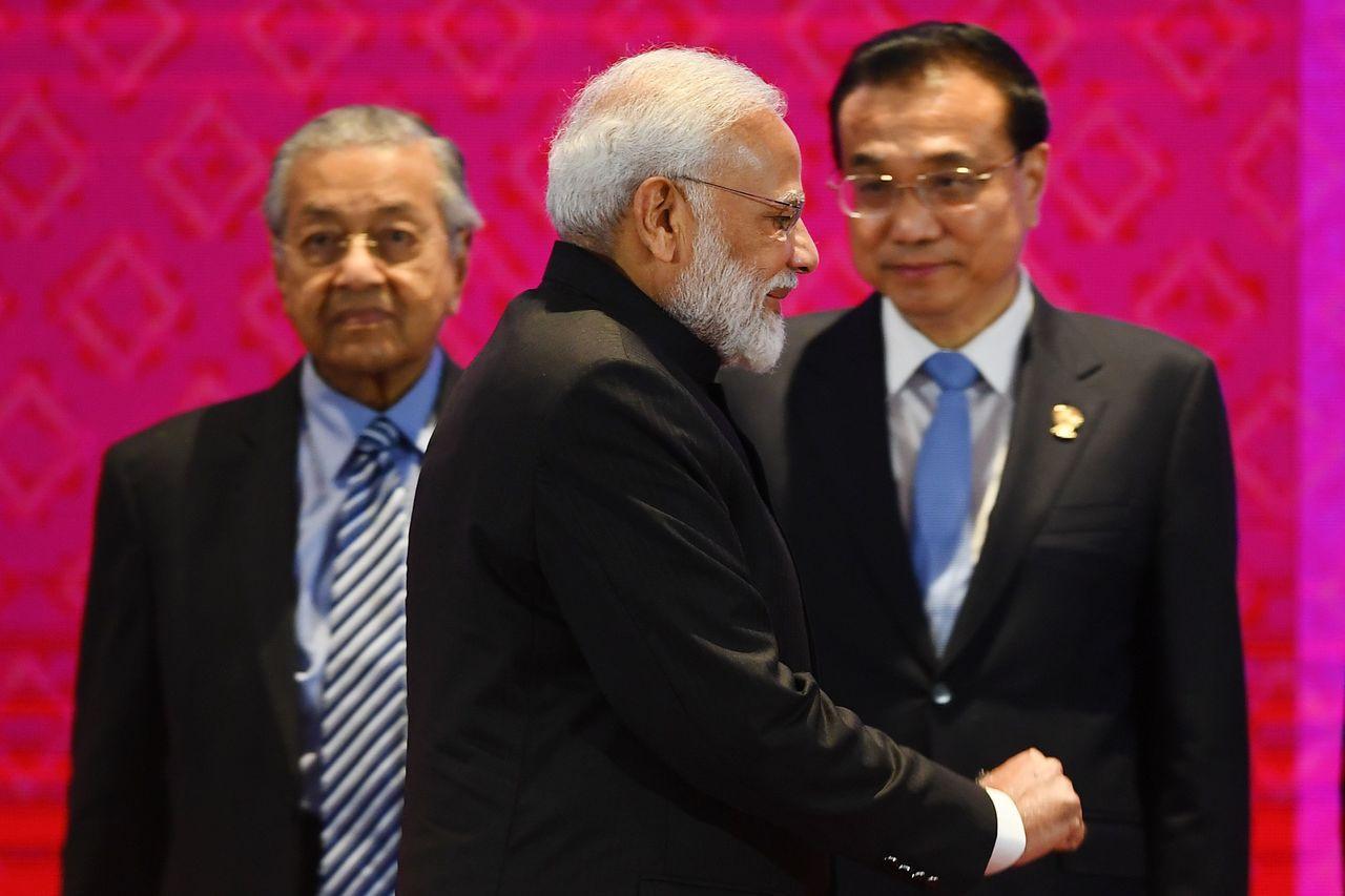 印度總理莫迪(左)4日在東 協峰會會場,從中國總理李克強( 右)前方走過。印度已...