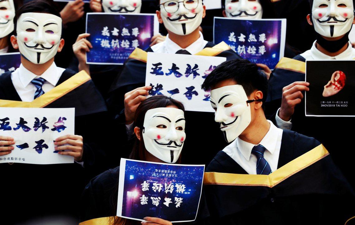 反送中第150天,香港理工大學畢業生手持標語、戴面具出席畢業典禮。「一幅握手合照...