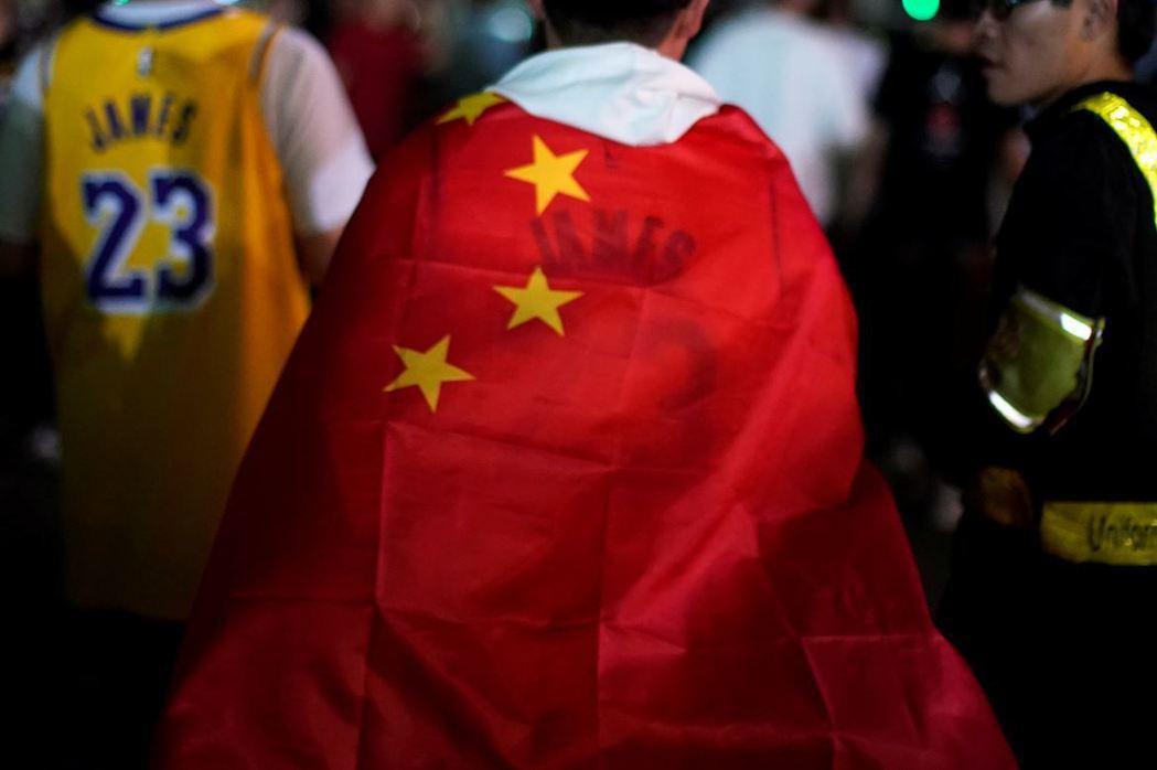 NBA中國熱身賽,因火箭隊GM莫雷一番「挺港」言論,導致NBA遭中國合作夥伴抵制。圖為一名中國觀眾身披五星旗進場觀賽。 圖/路透社