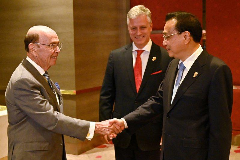 羅斯(左)4日在泰國曼谷東協峰會場合上跟中國總理李克強握手致意。路透
