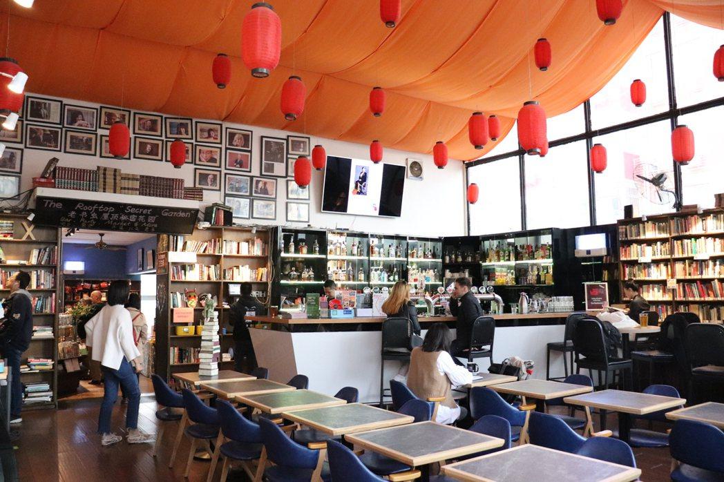 老書蟲店內一隅,紅色燈籠與大型玻璃窗照射的自然光,書牆上林立的書,加上吧檯與高腳...