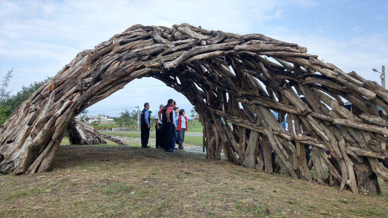 「加留沙浪」以漂流木創作流線型的自然雕塑,外型像沙丘,遊客行走其間,陽光從漂流木...