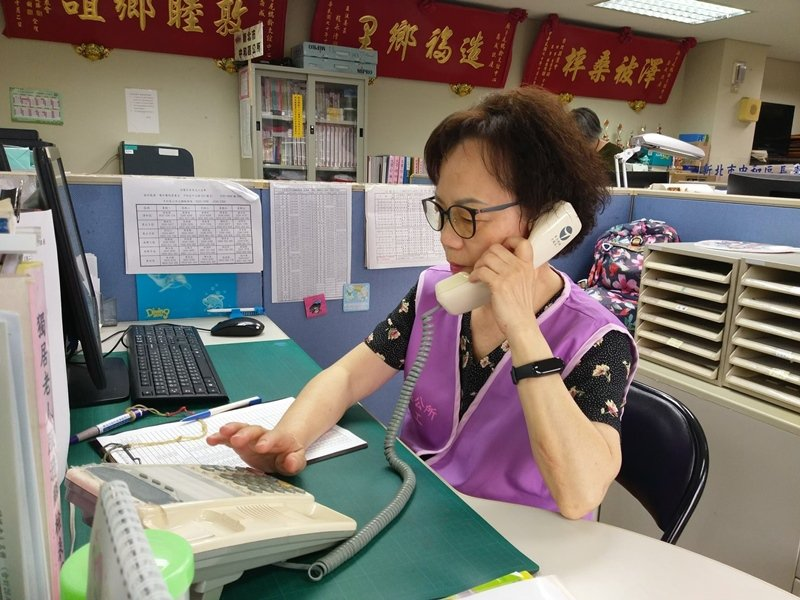 張麗英打電話與長者聯繫便當送達時間。 圖/新北社會局提供