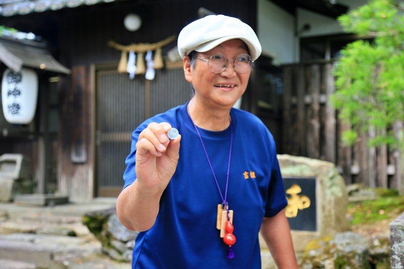 神社導覽人員解說日幣一元上的樹木由來。 圖/魏妤庭攝影