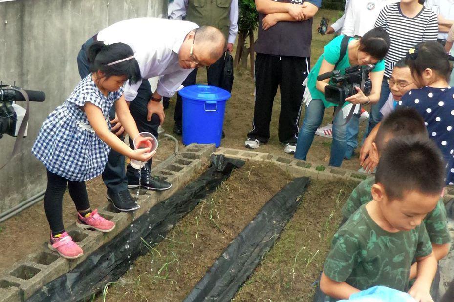 高雄市副市長葉匡時(左二)和學童一起撒種子、澆水種農作。記者林保光/攝影