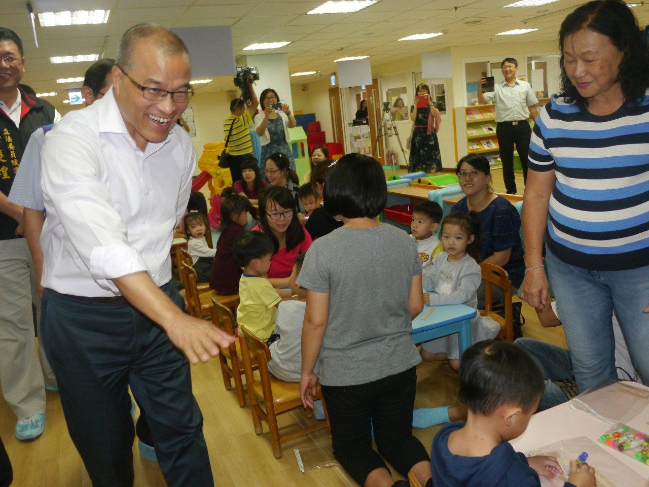 高市副市長葉匡時(左)到大寮公共托嬰中心暨育兒資源中心參訪,跟現場的家長與小朋友...