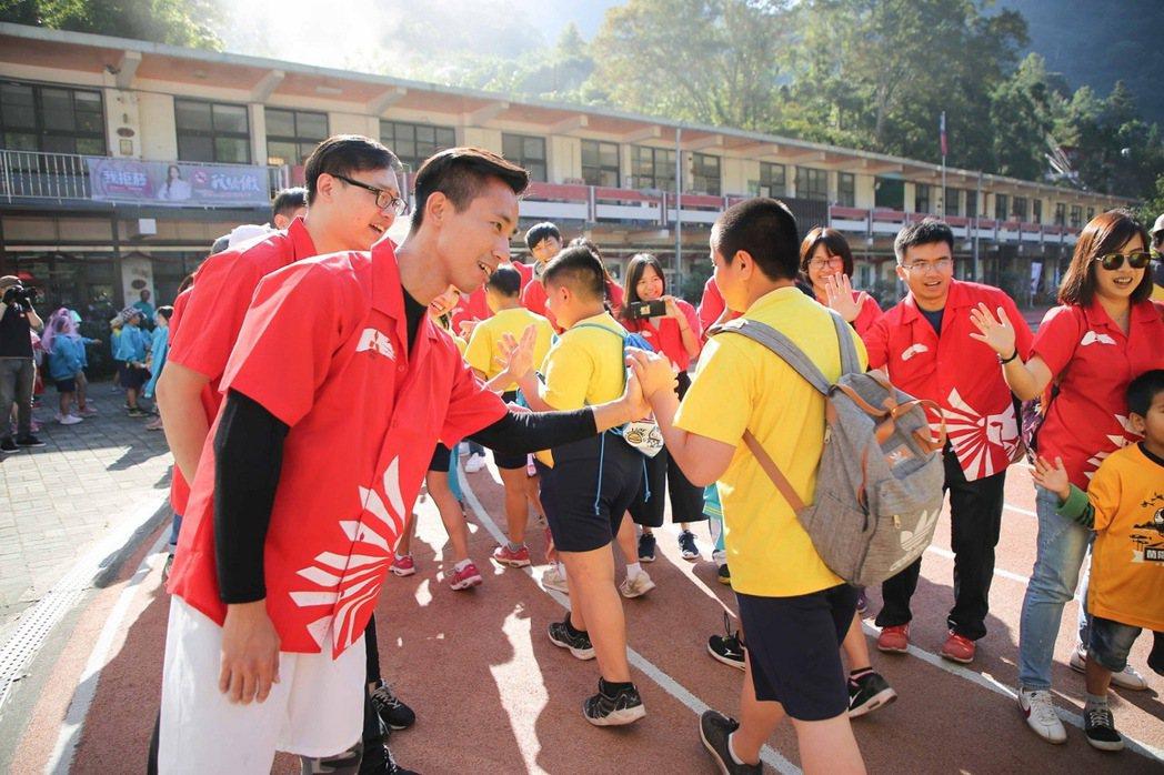 中華三菱志工列隊歡迎五峰國小小朋友參加跨校聯合運動。 圖/中華三菱提供