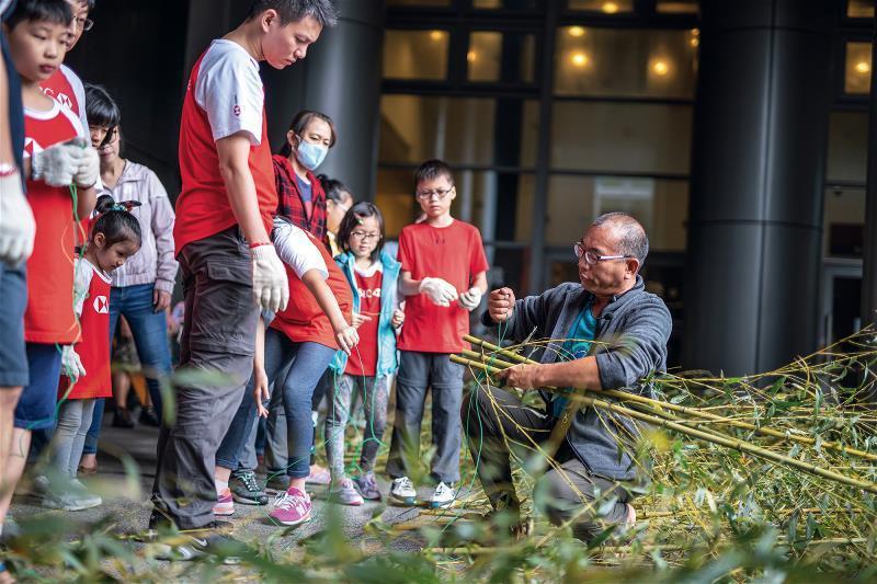 王銘祥帶領大人小孩將竹叢綁成軟絲產房,並藉機宣導保育觀念。 (林旻萱攝)