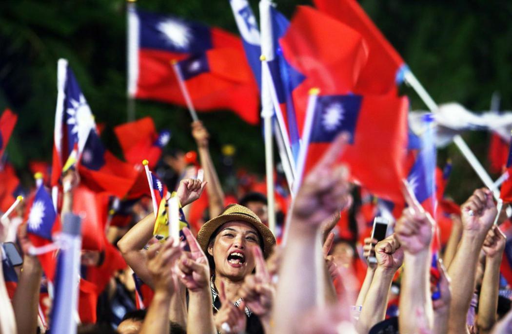 群眾手揮國旗。記者劉學聖/攝影