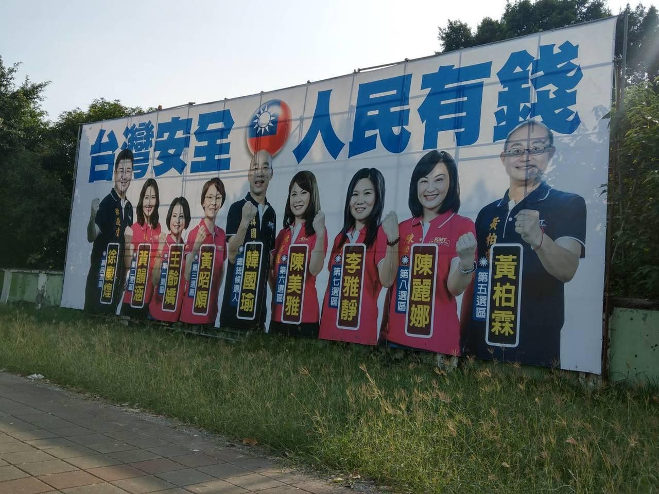 韓國瑜和國民黨提名8名立委參選人合體的大型看板,打出「台灣安全、人民有錢」的口號...