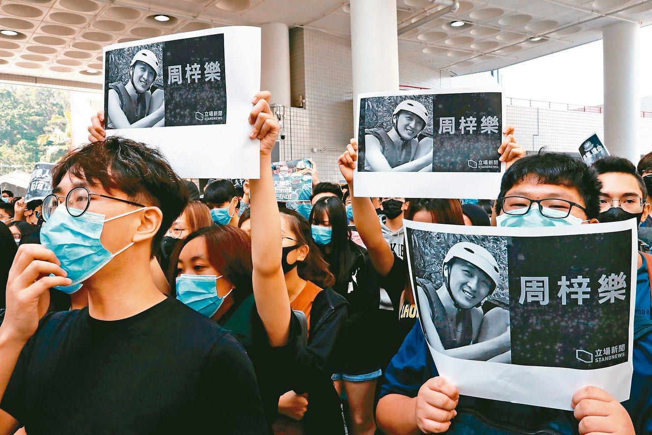 香港科技大學學生手持周梓樂的照片示威遊行。 (路透)