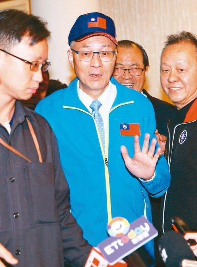國民黨主席吳敦義(中)考慮自提為下屆不分區立委,引發黨內質疑,昨被媒體追問,揮手...