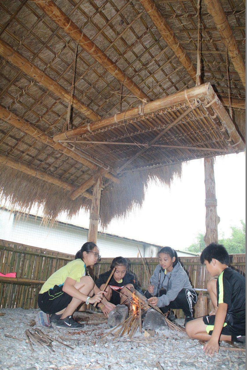 花蓮縣永豐國小學童,在兩棟阿美族傳統屋內學習祖生的生活智慧。圖/校長伍玉成提供