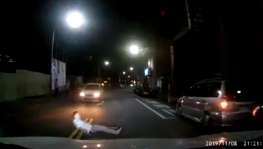 一名男子在新北市汐止區衝進車道,倒在兩輛行駛中汽車前方,隨即起身捶打地面後離開,...
