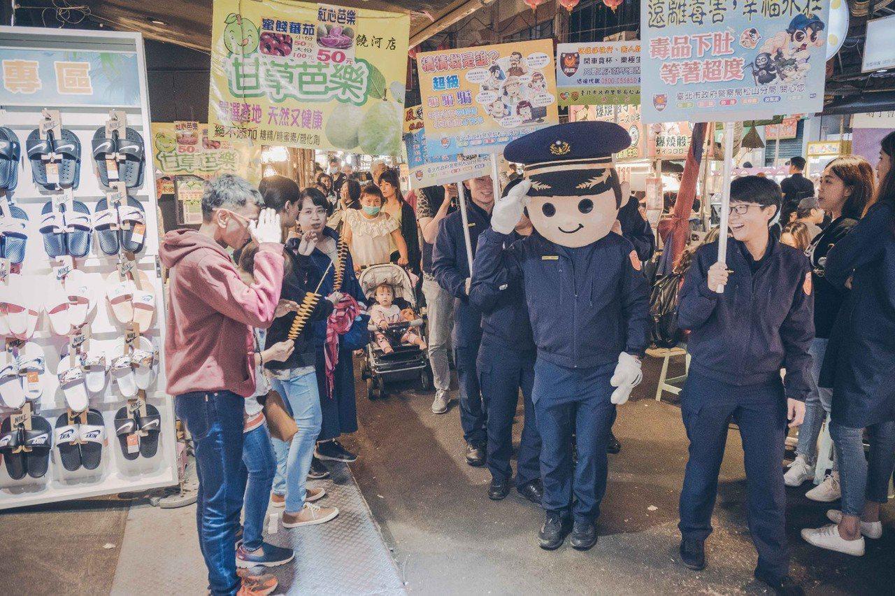 北市松山警方日前在饒河夜市宣導反毒、反賄選,現場還有警察娃娃,讓遊客紛搶合影。記...