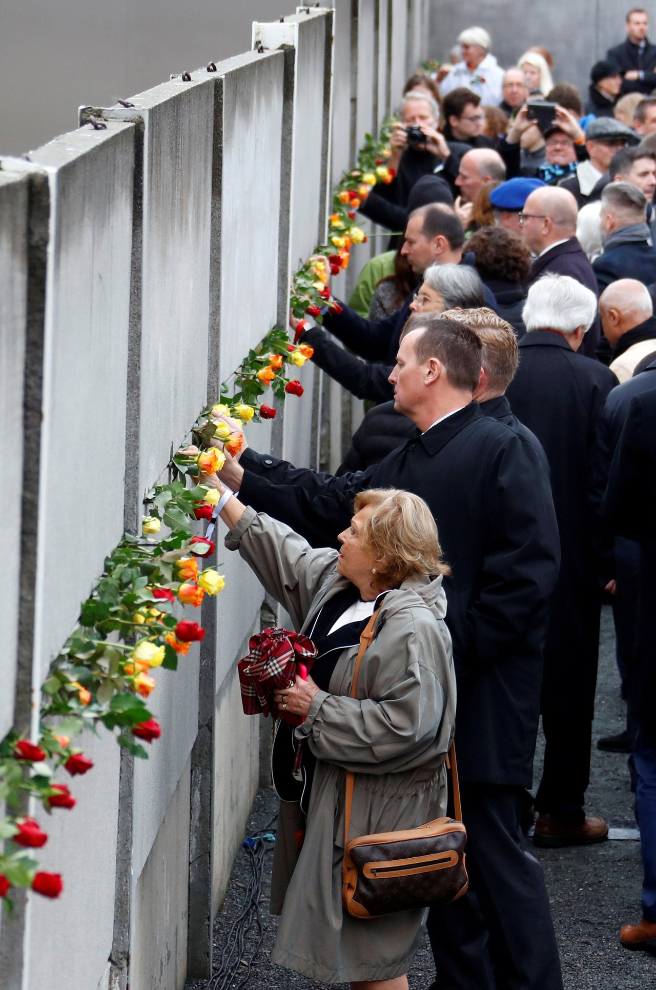 德國柏林圍牆倒塌30周年,德國領導人和與會者9日在柏林圍牆遺跡插上玫瑰哀悼因試圖...