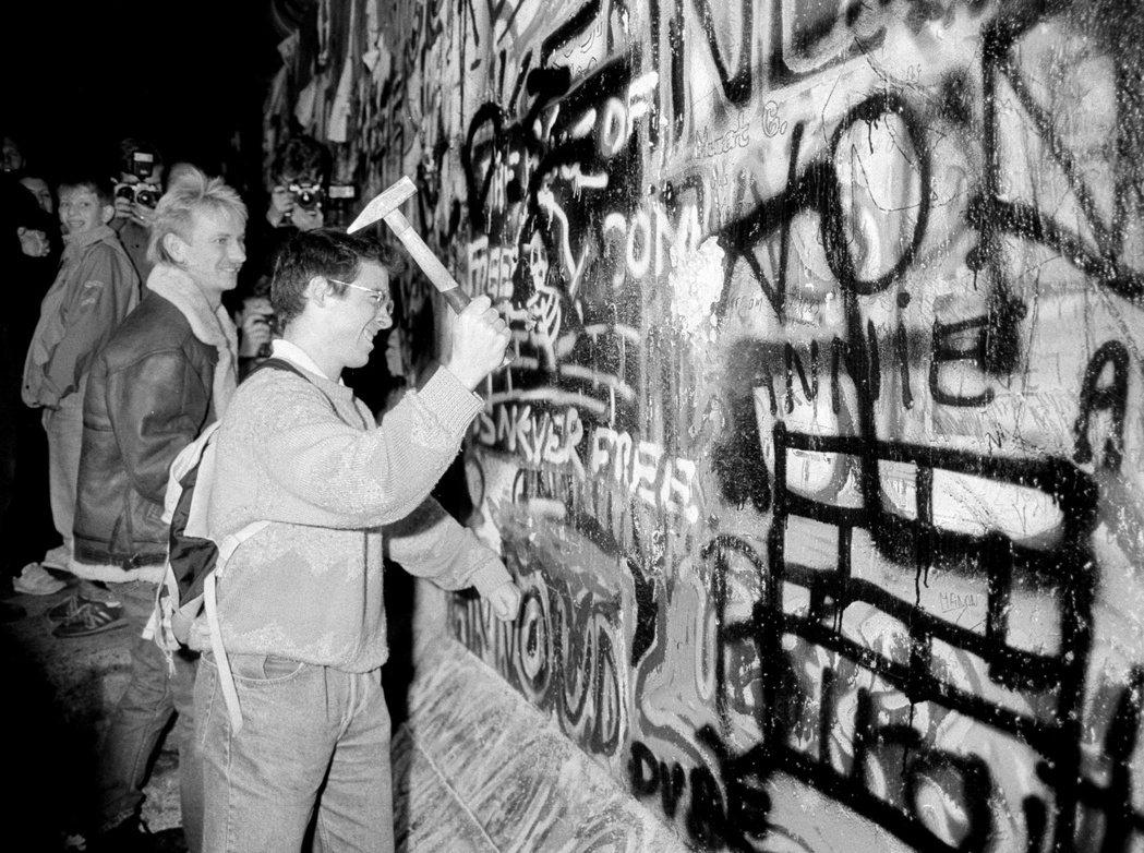 1989年11月9日,東德允許民眾從柏林圍牆進入西德,一名男子敲下布蘭登堡門附近...