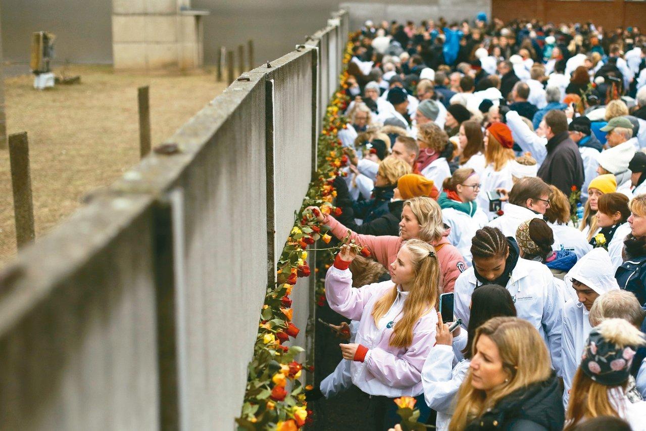 民眾九日把花朵插在柏林圍牆遺跡上,紀念東德恐怖統治的受害者。 (美聯社)