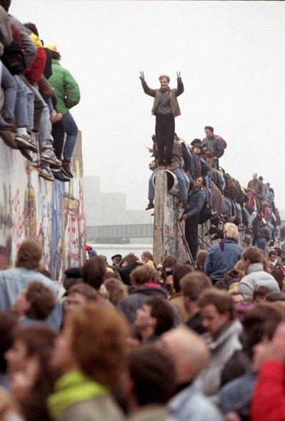 一九八九年十一月九日柏林圍牆倒塌後,民眾連日穿越圍牆進入西柏林,大批民眾十二日爬...