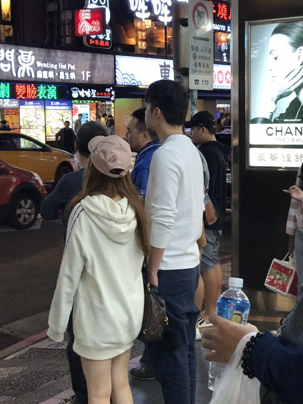 周洺甫偕一名長髮妹現身西門町,正等待紅綠燈過馬路。圖/讀者提供