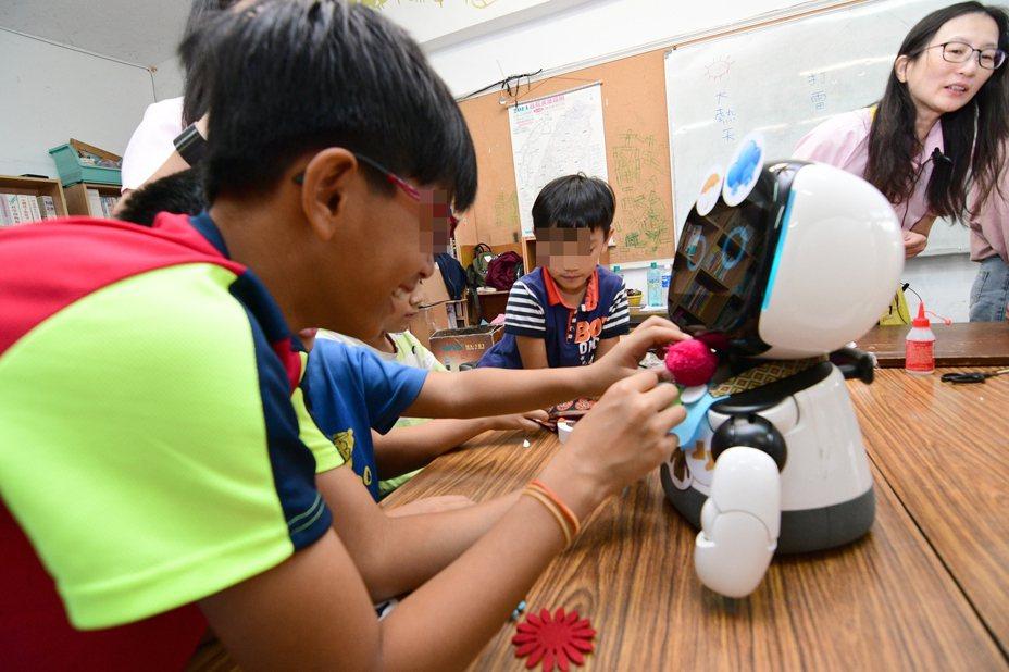 台東孩子的書屋裡的小朋友開心圍著AI機器人,幫機器人戴上原住民裝飾。記者羅紹平/攝影