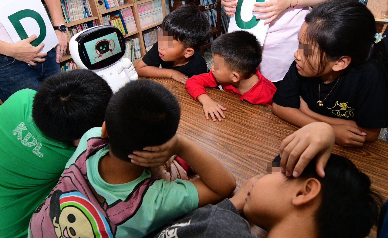 台東孩子的書屋裡的小朋友開心圍著AI機器人,跟著機器人學英語。記者羅紹平/攝影