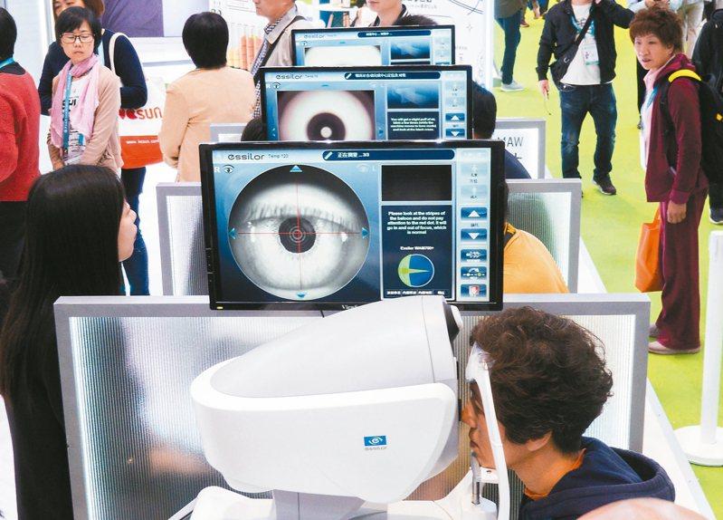 第二屆進博會醫療器械及醫藥保健展區依視路展台,觀眾體驗WAM700七合一眼健康篩查儀。這款全自動眼部健康篩查儀可以快速完成白內障、青光眼、圓錐角膜三種眼健康篩查和屈光度、波前像差、角膜地形圖等7項全方位眼健康評估。 新華社