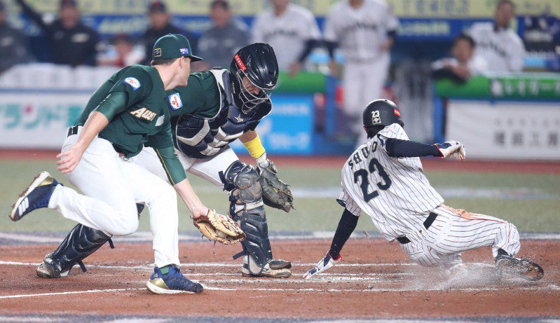 2019第2屆世界12強棒球錦標賽複賽,11日晚間在千葉球場進行澳洲隊與日本隊的賽程,日本打者源田壯亮7局下採用短打強迫取分,讓三壘跑者周東佑京(右)滑回本壘,助隊追平比數。中央社