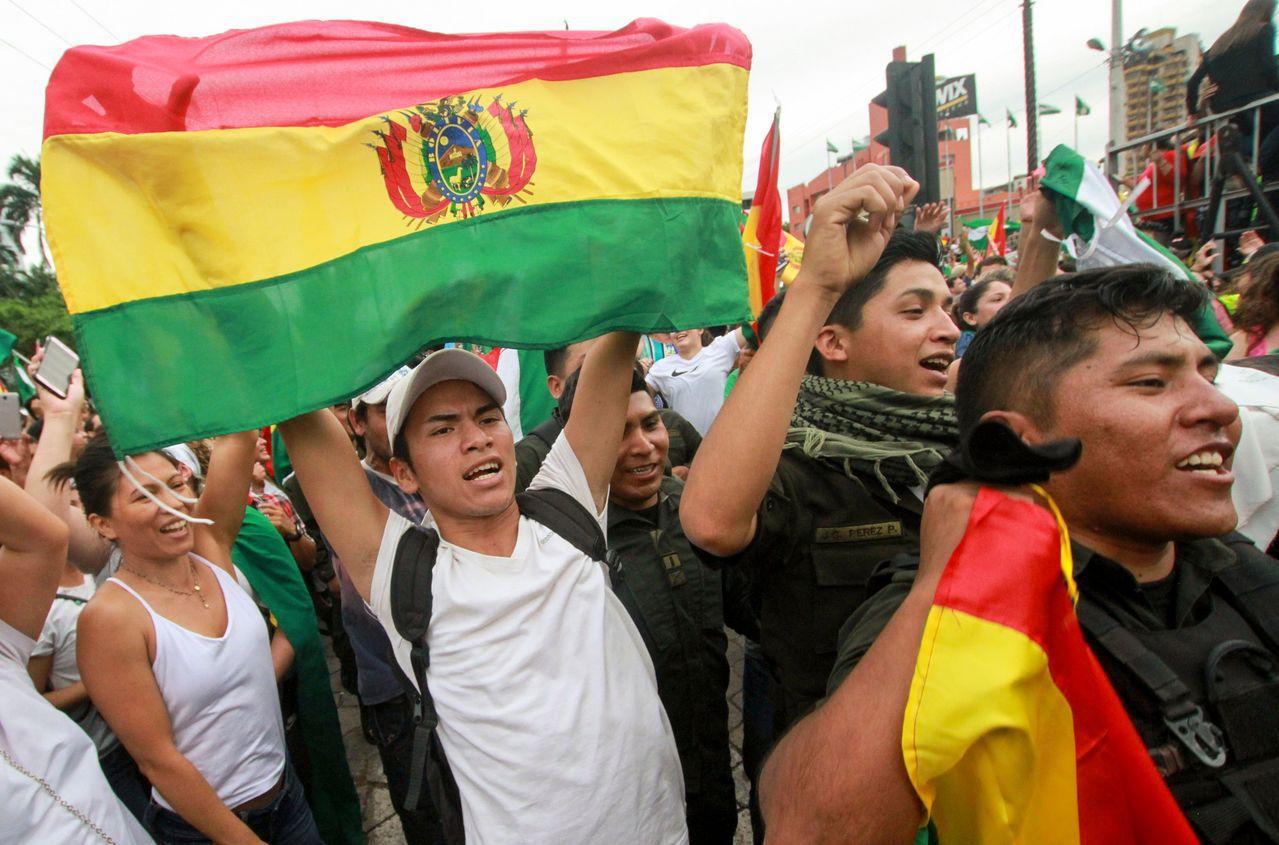 玻利維亞群眾10日在最大城聖克魯斯街頭慶祝總統莫拉萊斯下台。(法新社)