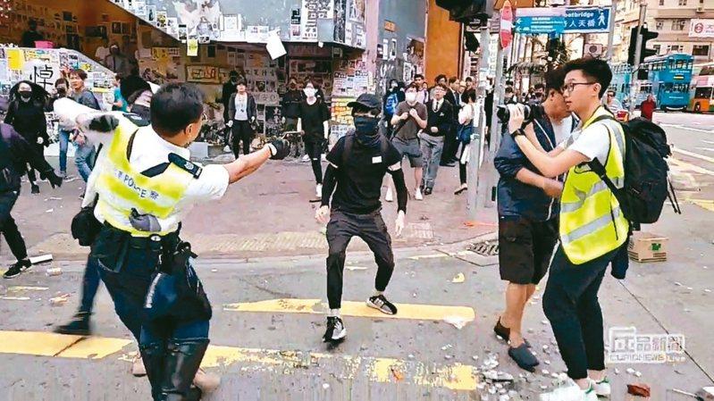 社群媒體的畫面顯示,港警11日在西灣河朝民眾開槍,一名交警左手抱著白衣男子,右手持槍朝黑衣男子腹部射擊。 路透