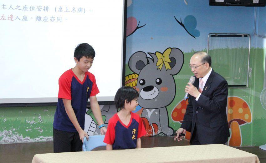 講師柯金發(右)指導學生用餐時入座禮儀。 富偉科技集團/提供