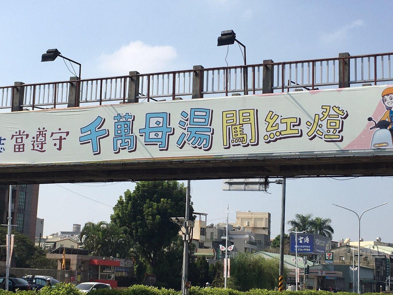 市府懸掛交通宣導布條寫著「千萬母湯闖紅燈」,市議員蔡文旭認為是錯誤用字。圖/蔡文...