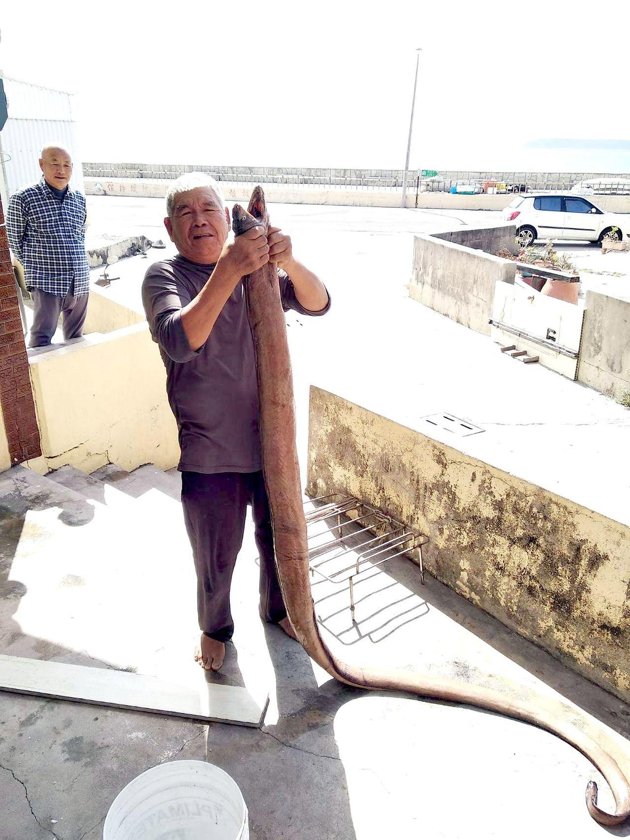澎湖漁民陳文騫意外捕獲的怪魚,長達3公尺,抓在手裡,還一大截拖在地上。圖/陳文騫...
