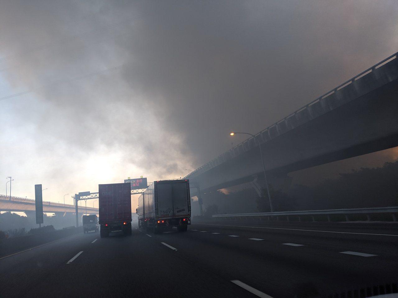 桃園市龜山區資收場火警,大量濃煙飄向一旁的國道一號林口路段。圖/楊姓讀者提供
