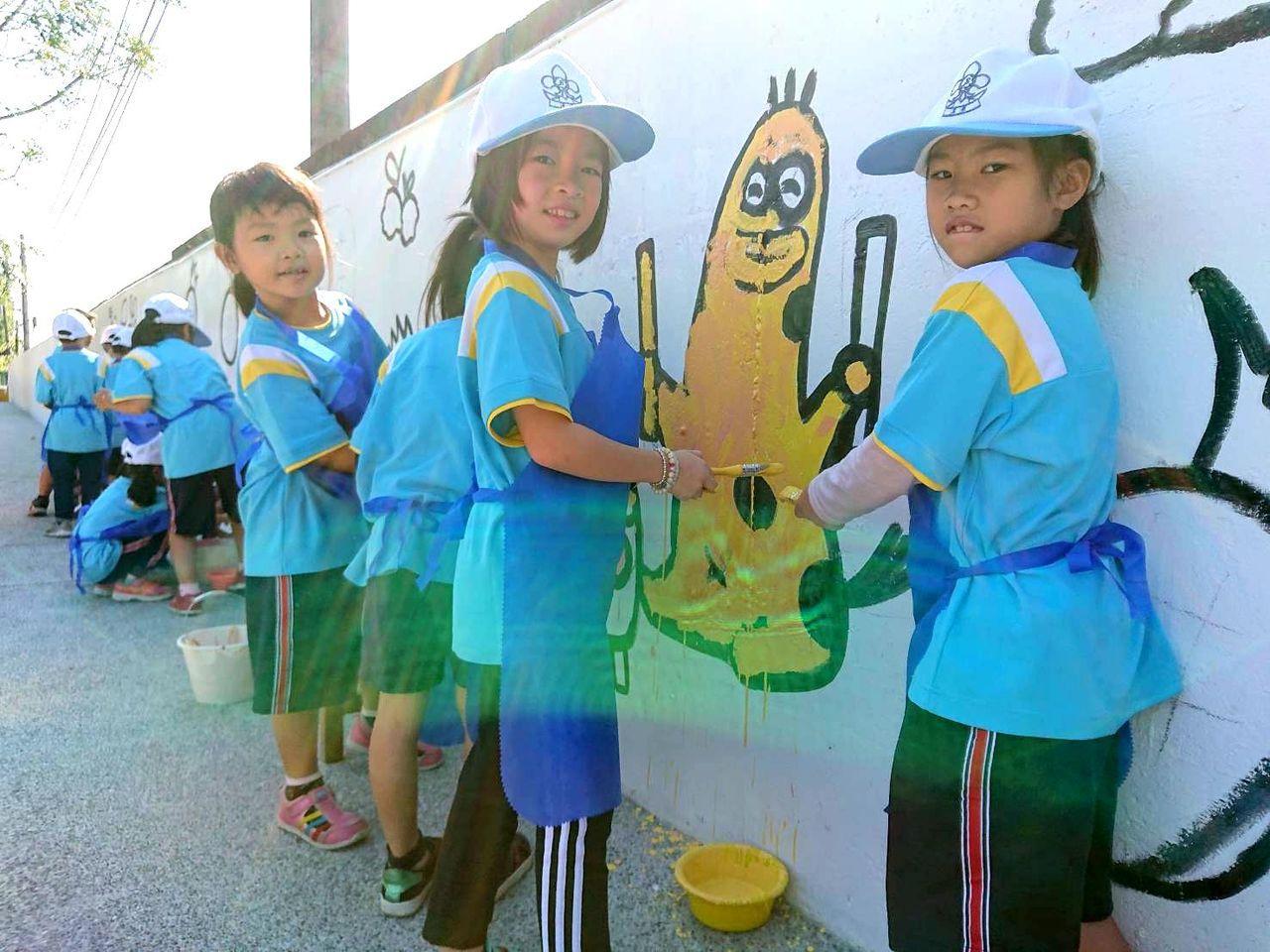在知名插畫家「鱷魚先生」指導下,高雄大樹溪埔國小學童參與圍牆彩繪。記者王昭月/翻...