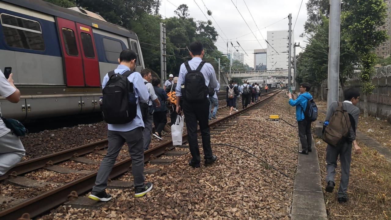 香港鐵路部分路段12日上午再傳遭破壞,乘客被迫沿著鐵軌步行回沙田站。(港鐵提供香...