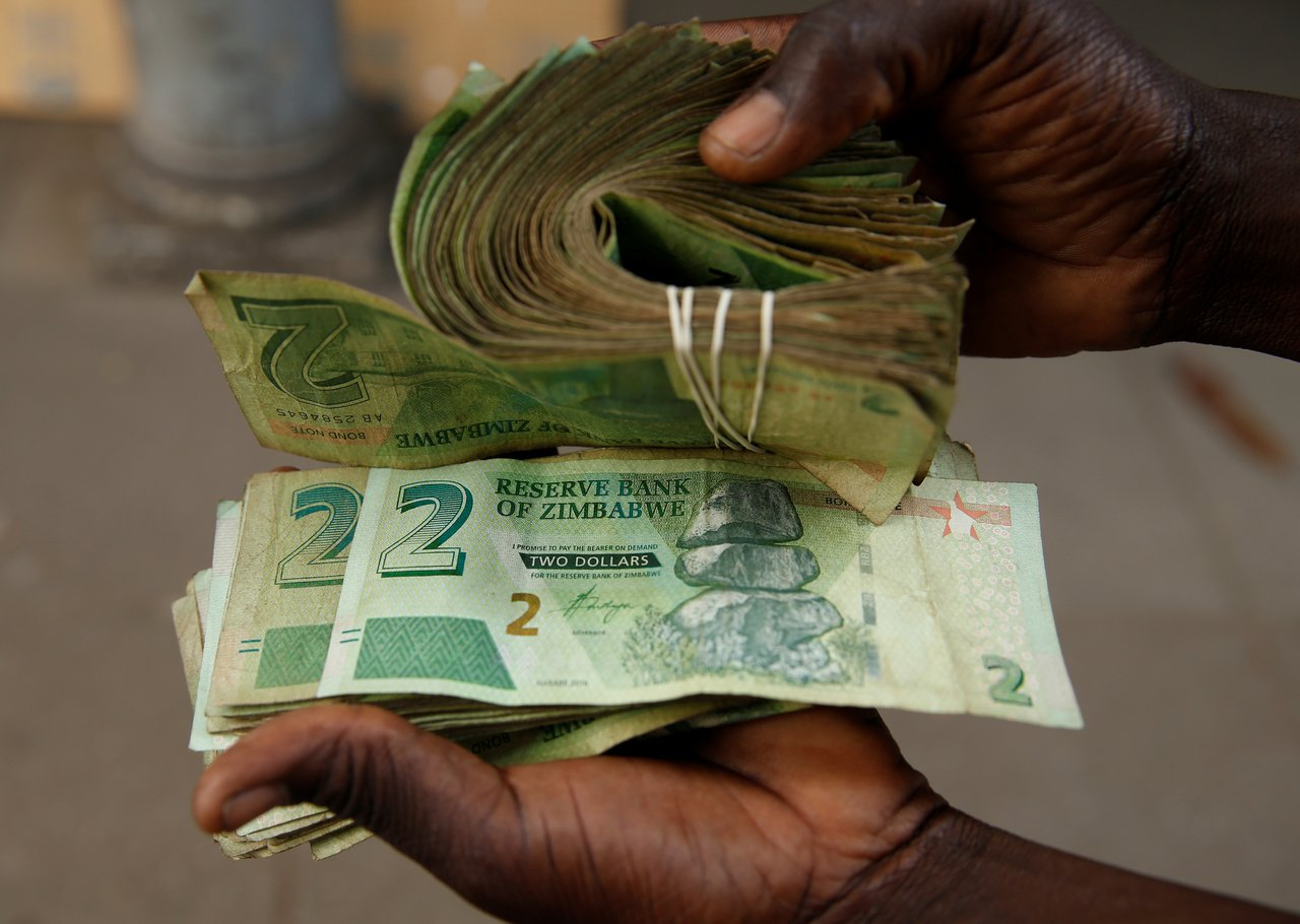 辛巴威原定11日開始發行新貨幣辛巴威元,但銀行未收到。圖為街頭小販展示舊有的債券...