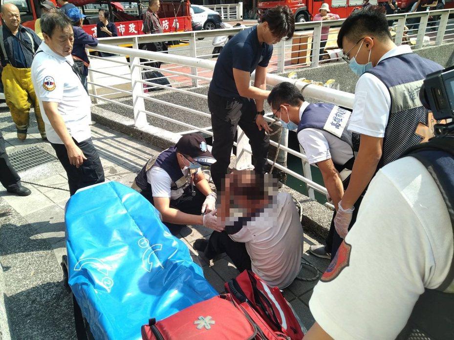 陳姓男子落水後頭部撞及水下河床,消防隊將他救上岸,救護員正為他檢傷。記者林保光/翻攝