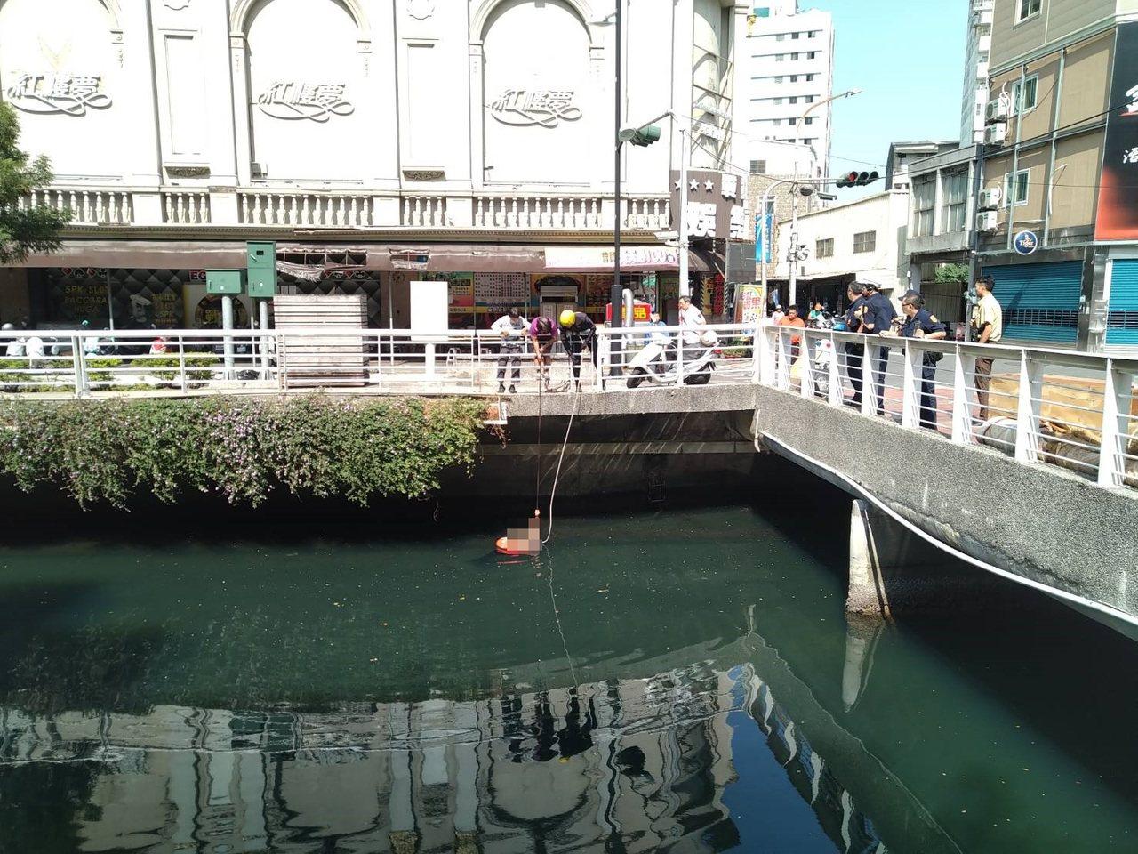 陳姓男子今天在高雄幸福川落水,1婦人和消防隊以繩索拉住他。記者林保光/翻攝