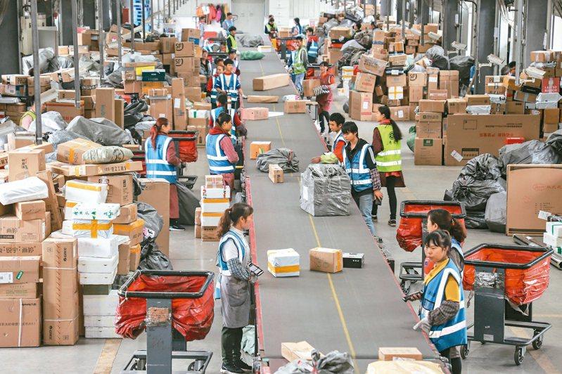 中國國家郵政局監測數據統計,11月11日當天,大陸全國各郵政、快遞企業共處理5.35億快件,同比增長28.6%,再創歷史新高。圖為貴州順豐速運有限公司王寬分撥中心,工作人員正在分揀快遞。 中新社