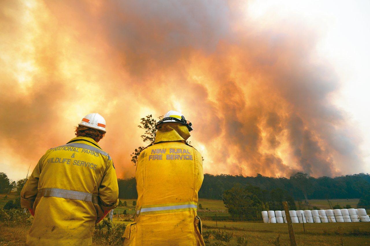 澳洲東部科夫港一處野火火勢驚人,兩名消防人員十二日保持距離警戒。 路透